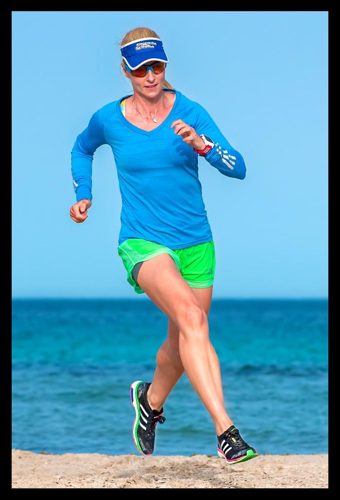 Triathletin beim Lauftraining am Strand mit Meer im Hintergrund im Runners Flow