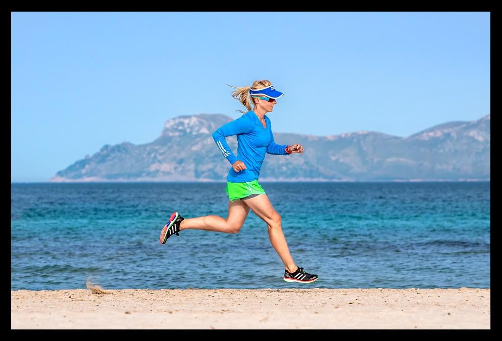 Triathletin beim Lauftraining am Strand mit Meer im Hintergrund im Runners High