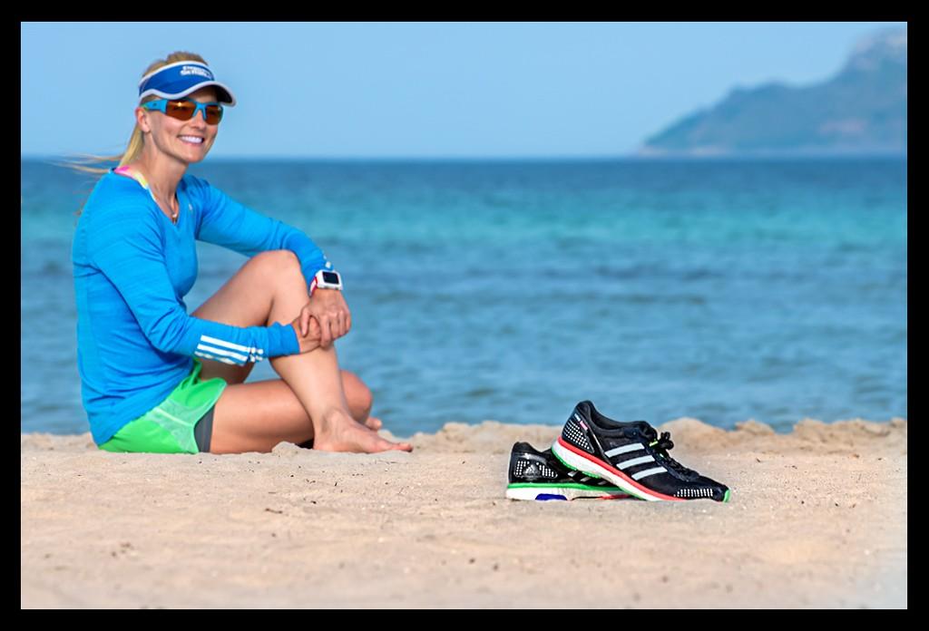 Läuferin sitzend am Strand mit Meer im Hintergrund und Laufschuhe im Vordergrund