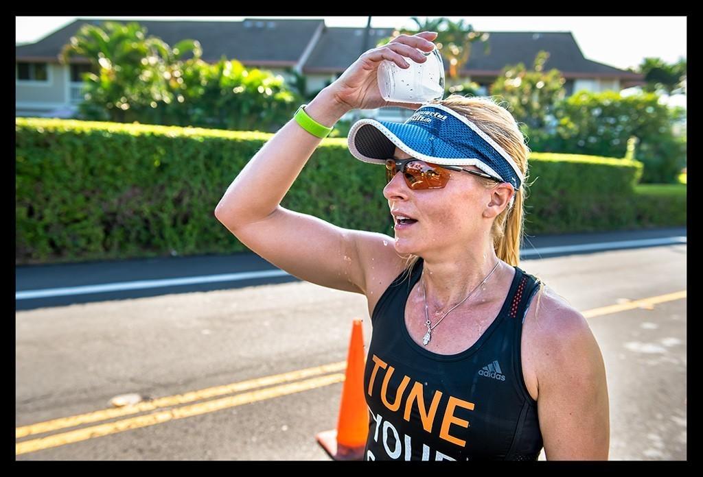 Läuferin mit Wasser über dem Kopf beim Hawaii - Big Island 10k Path Run