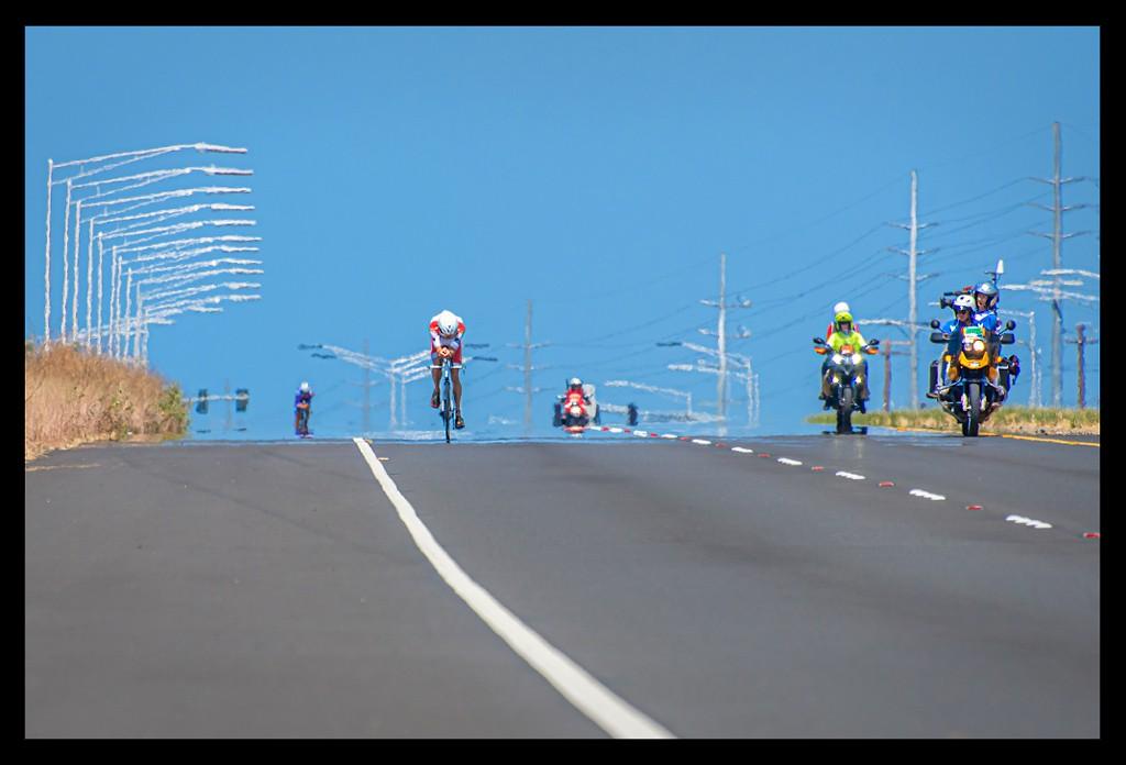 Ironman Weltmeisterschaft Jan Frodeno in Kona auf der Radstrecke auf der Landstraße vor Ozean und Himmel und Lava