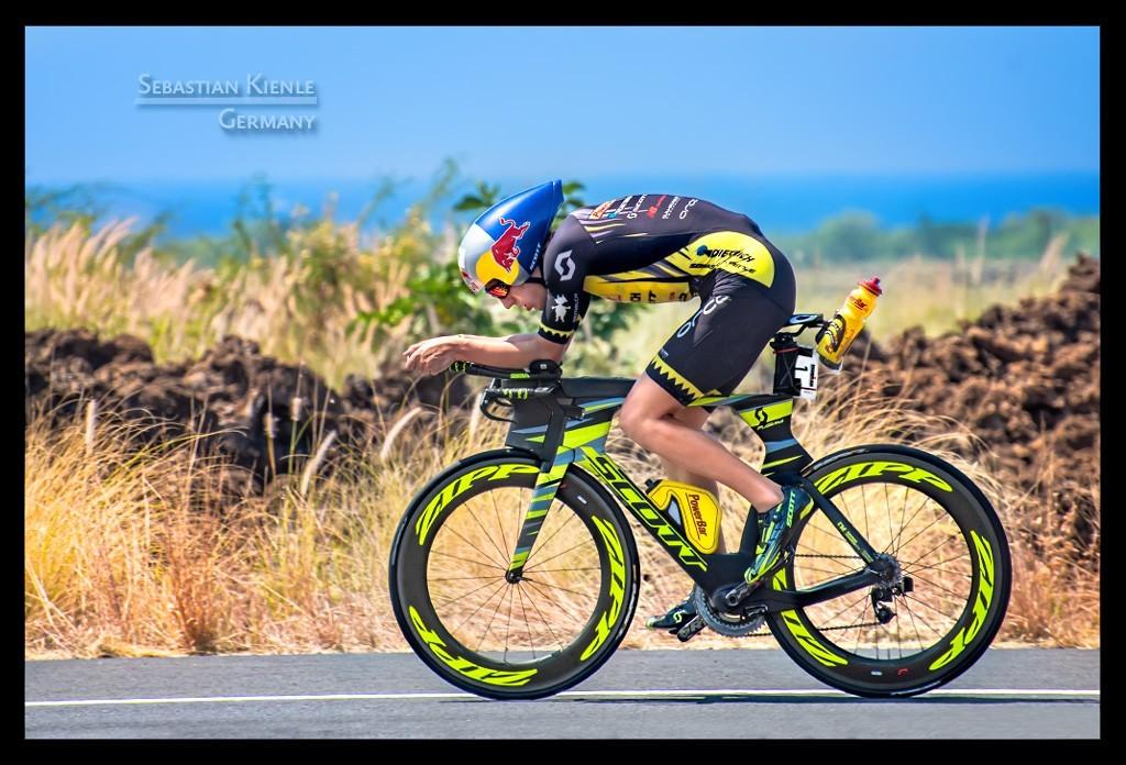 Ironman Weltmeisterschaft Sebastian Kienle in Kona auf der Radstrecke auf der Landstraße vor Ozean und Himmel und Lava