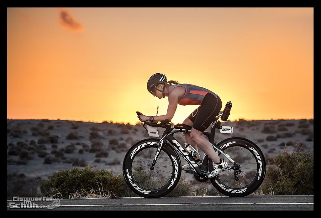 Triathletin im Tri Suit auf Zeitfahrrad im Sonnenuntergang