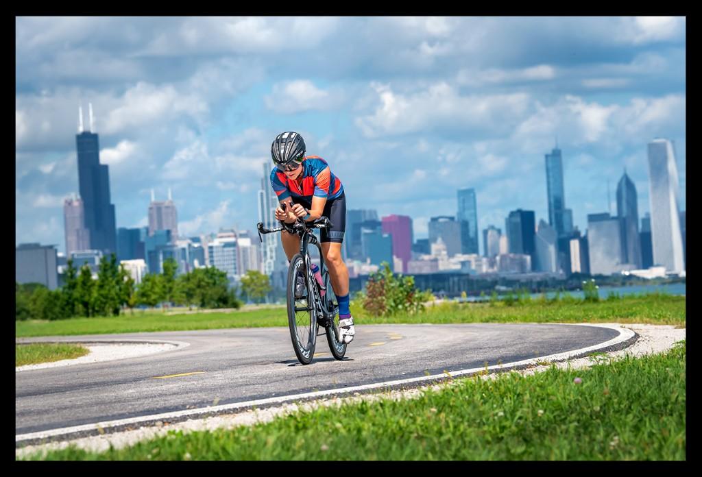 Triathletin beim Radtraining auf Zeitfahrrad Skyline Chicago im Hintergrund