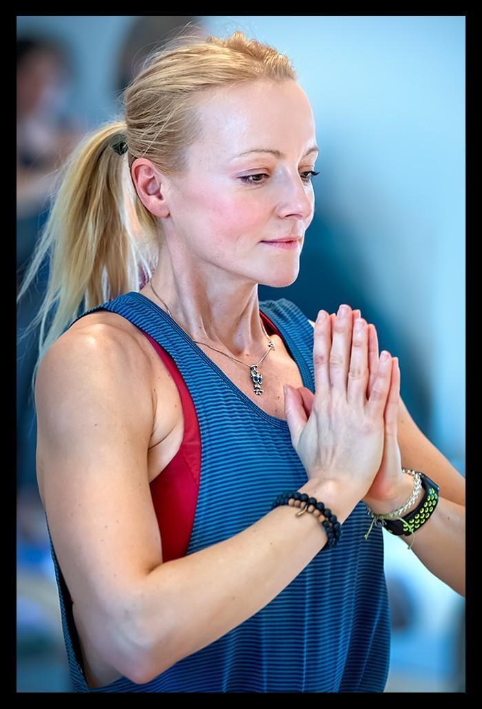 Yogini auf der Yogamatte für mehr Selbstfürsorge und muskuläre Entspannung beim Triathlon Training