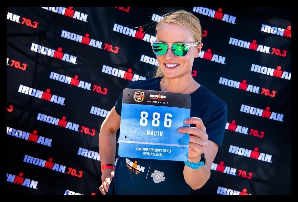 IRONMAN Florida Langdistanz blonde Frau Athletin mit Sonnenbrille lächelnd mit Startnummer vor Logo Ohana Wand