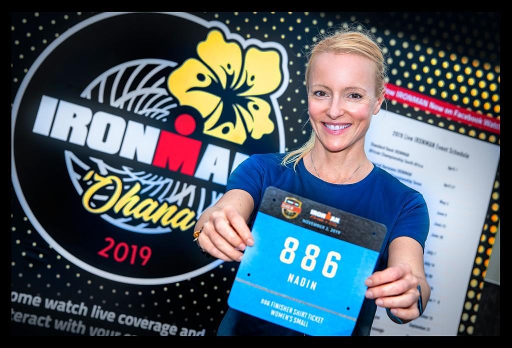 IRONMAN Florida Langdistanz blonde Frau Athletin mit Startnummer vor Logo Ohana Wand lachend