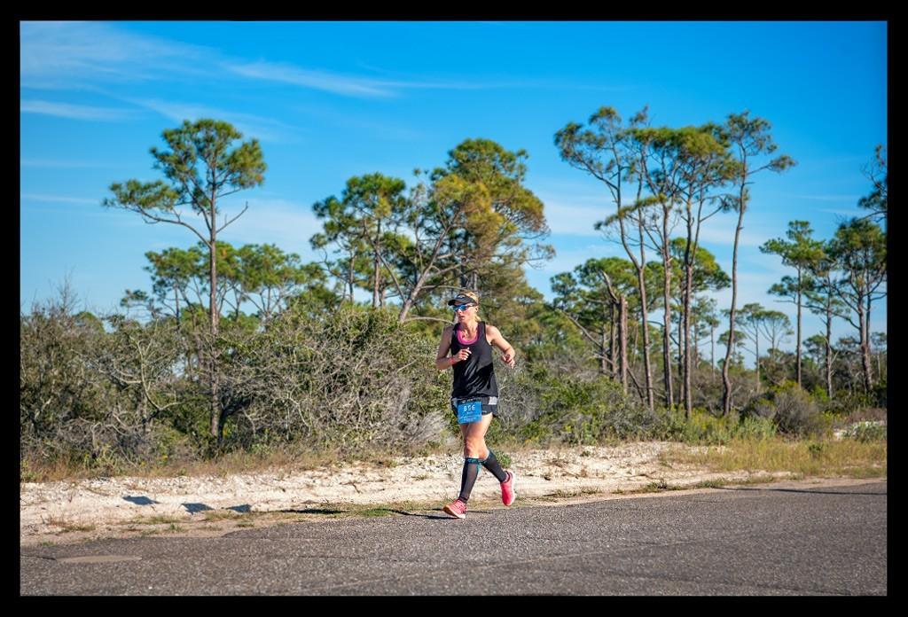 Ironman Florida St Andrews State Park Triathletin laufend auf Straße