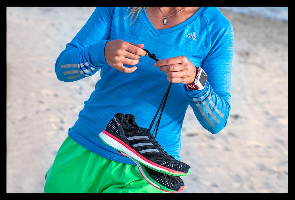 Frau beim Lauftraining am Strand mit Mittelmeer im Hintergrund auf Mallorca mit kurzer Laufhose und Laufshirt
