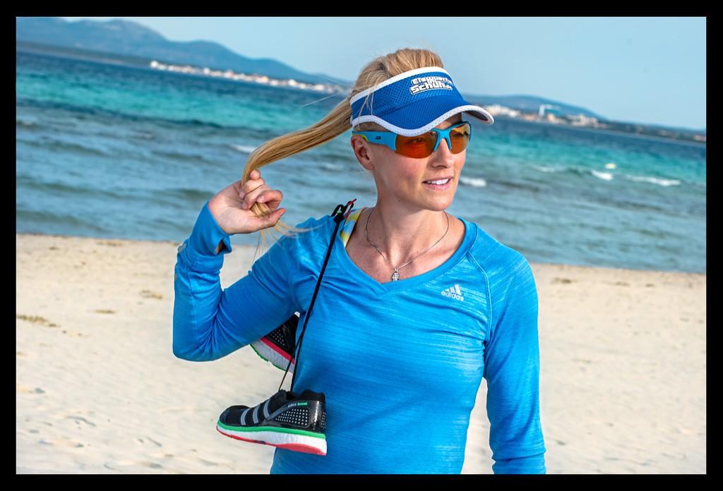 Frau beim Lauftraining am Strand mit Mittelmeer im Hintergrund auf Mallorca mit Sonnenbrille und Laufshirt