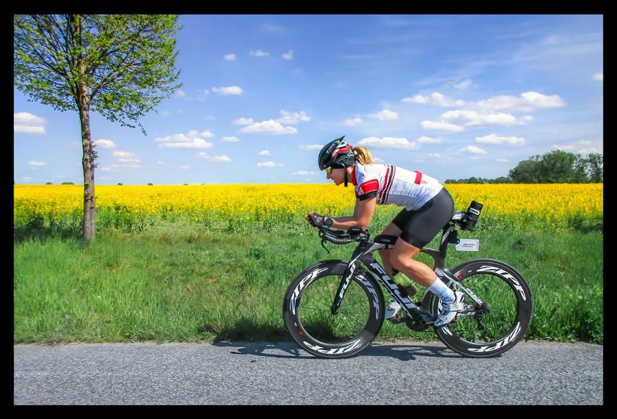Triathletin auf Zeitfahrrad vor Rapsfeld und blauem Himmel