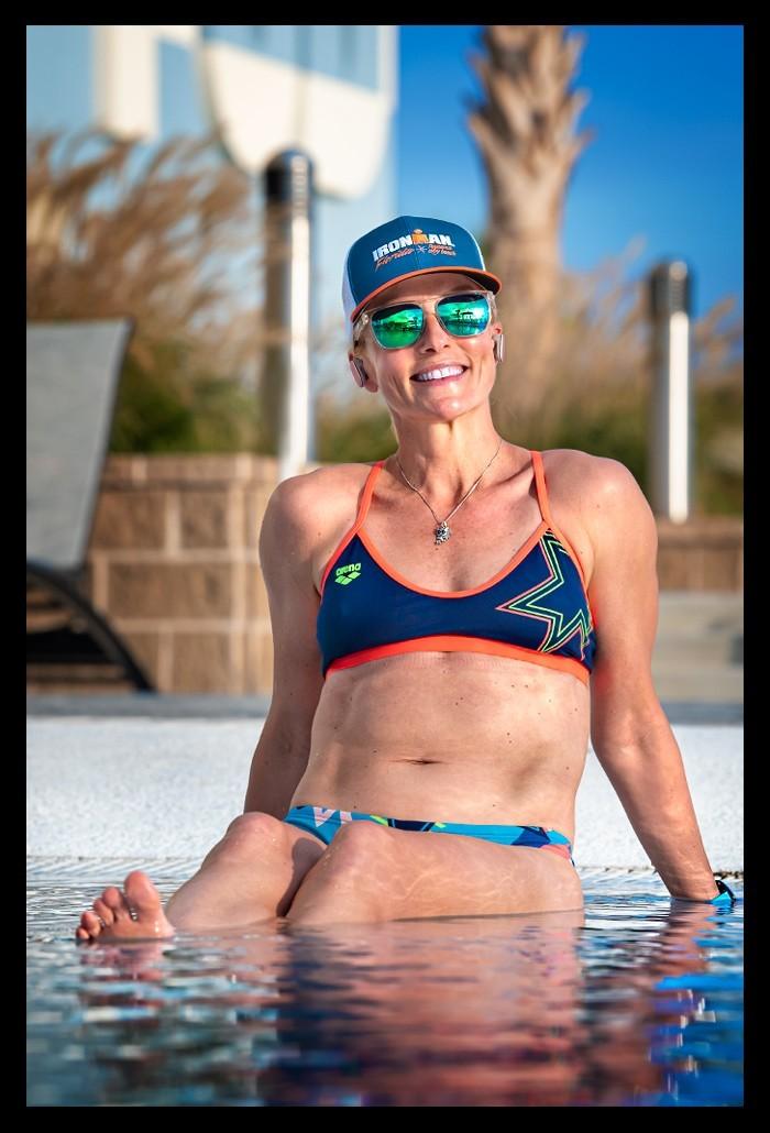 Triathletin Im Pool mit Basecap und Sonnenbrille entspannt lächelnd