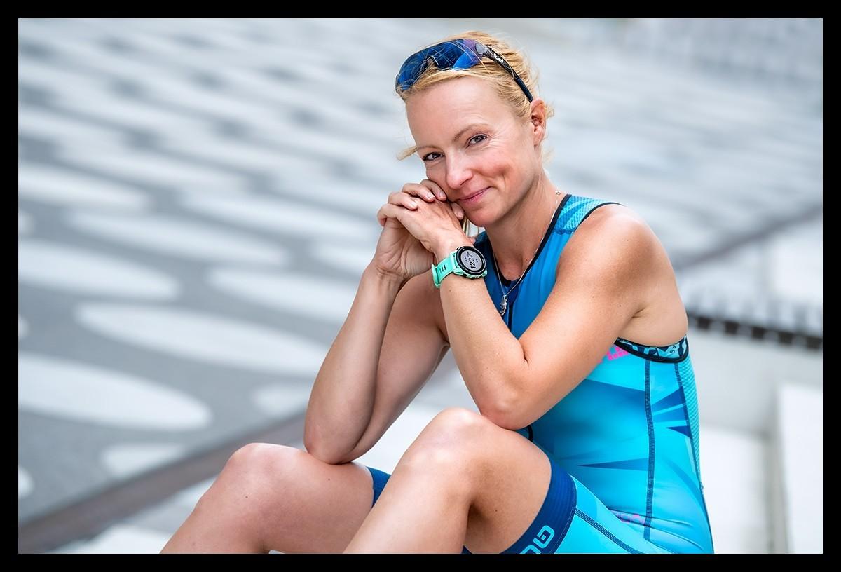 Triathletin sitzt im TriSuit auf Stufen nach dem Training mit Garmin Forerunner 745 am Arm und Sonnenbrille auf Kopf