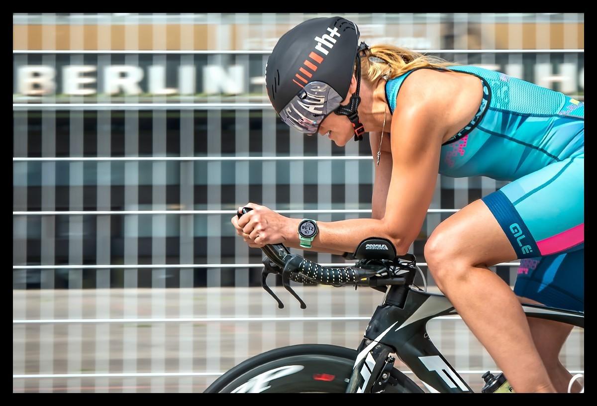 Triathletin beim Radtraining Berliner Tempelhofer Feld auf Zeitfahrrad mit Aero Helm TriSuit Garmin Triathlonuhr