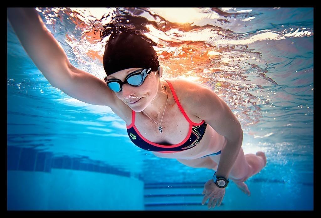 Triathletin beim Schwimmtraining im Pool mit Badekappe und Schwimmbrille unter Wasser Aufnahme
