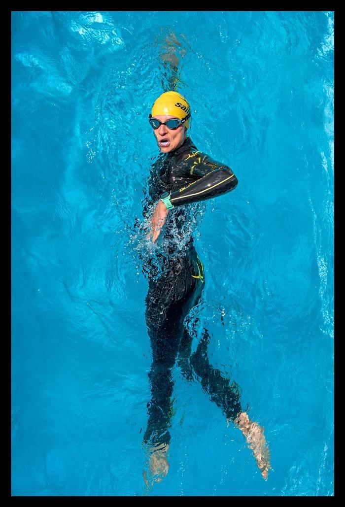 Triathletin vor Schwimmtraining im Wasser mit Neoprenanzug Schwimmbrille Badekappe und Garmin Multisportuhr