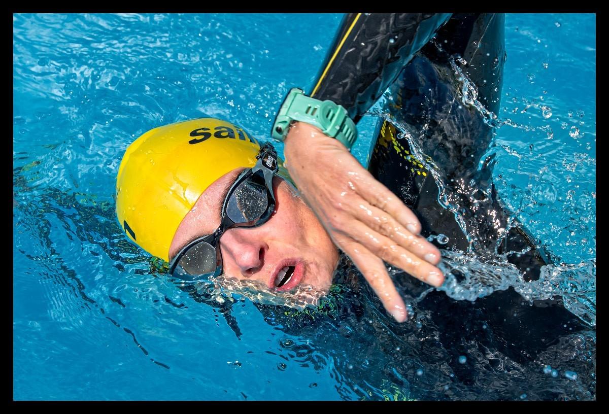 Closeup Porträt Triathletin vor Schwimmtraining im Wasser mit Neoprenanzug Schwimmbrille Badekappe und Garmin Multisportuhr