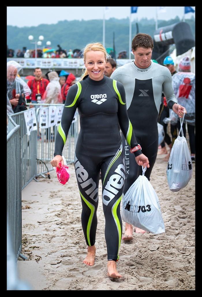 Triathletin im Arena Wetsuit Carbon Neoprenanzug am Strand mit Wechselbeutel