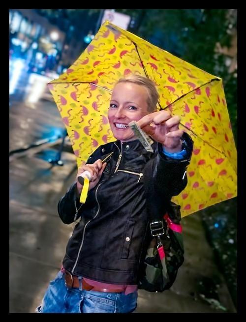 Frau lachend mit Dollarschein im Regen mit Regenschirm