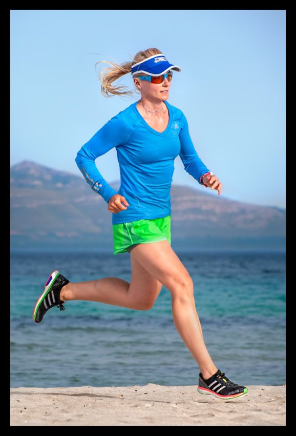 Triathletin beim Lauftraining mit kurzer Hose und langem Laufshirt und Laufschuhen am Strand Mallorca