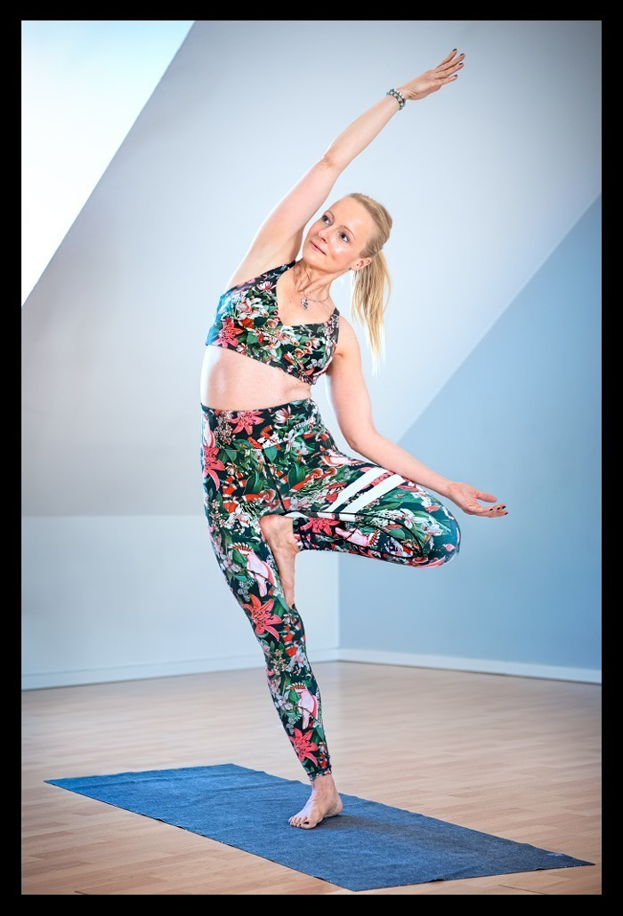 Yoga Tipps Frau in Baum Asana in Yogastudio mit Leggings und BH