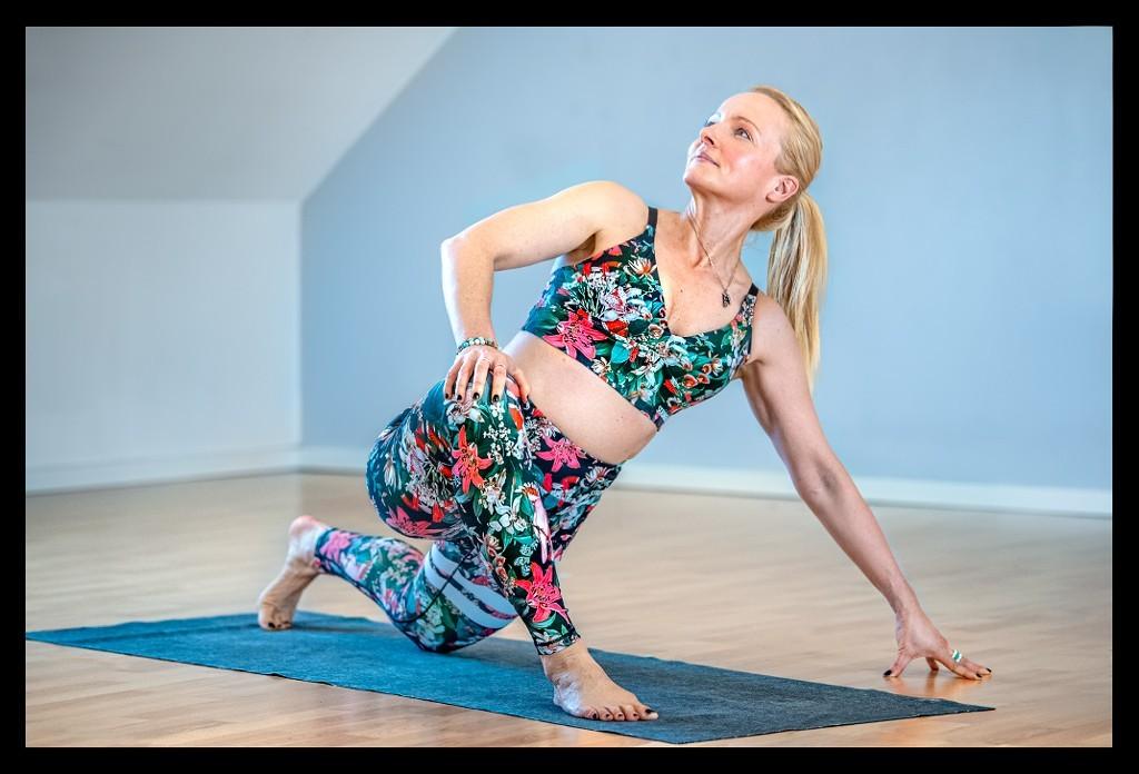 Yogalehrerin Frau auf Yogamatte im Yogastudio mit Leggings und BH in Eidechse verdrehte Leistenöffnung