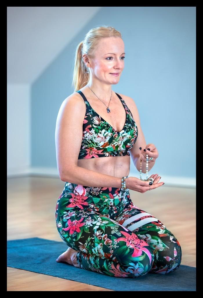 Yogalehrerin in Meditationshaltung mit Mala Kette lächelnd