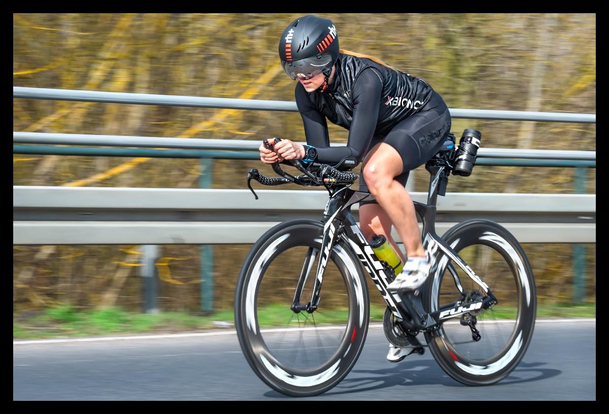 Radsportlerin auf Zeitfahrrad mit schwarzer Bekleidung und Helm und Garmin Rally Wattmesser Powermeter Sportfotografie