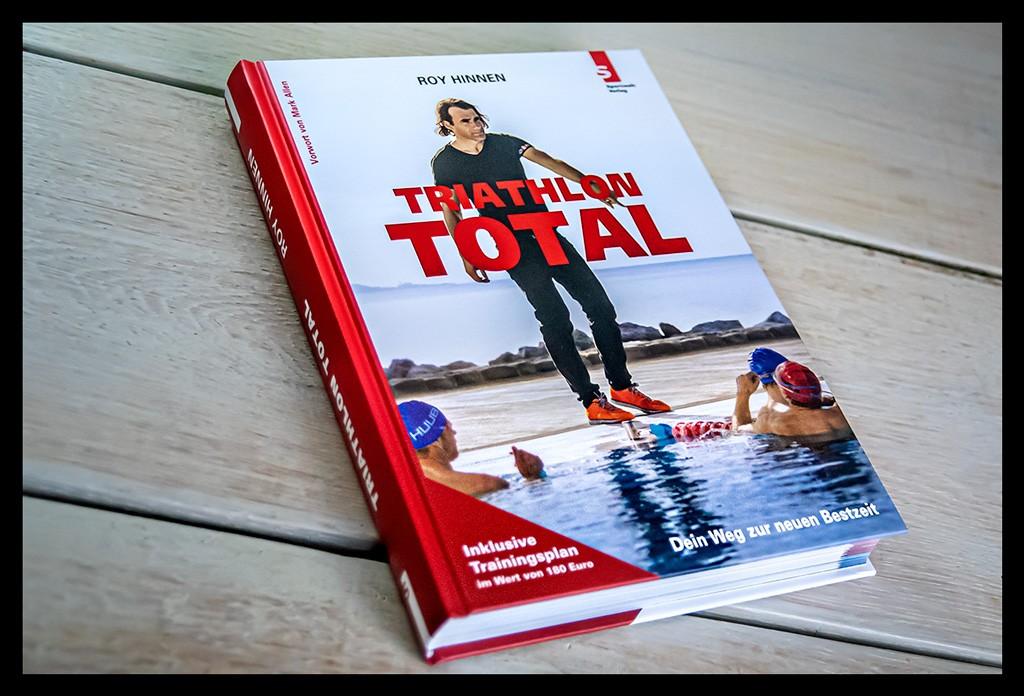 Triathlon Total: Dein Weg zur neuen Bestzeitvon Roy Hinnen Buchempfehlung Cover. Das Buch liegt auf einem Holztisch