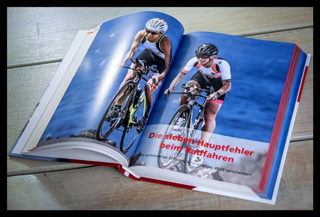 Triathlon Total: Dein Weg zur neuen Bestzeitvon Roy Hinnen Buchempfehlung Innenseite Radsportler. Das Buch liegt auf einem Holztisch und eine Seite ist aufgeschlagen.