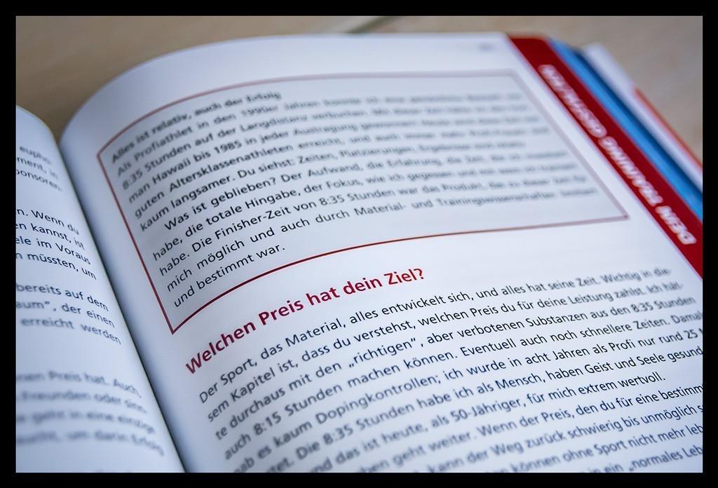Triathlon Total: Dein Weg zur neuen Bestzeitvon Roy Hinnen Buchempfehlung Textabbildung. Das Buch liegt auf einem Holztisch und eine Seite ist aufgeschlagen.