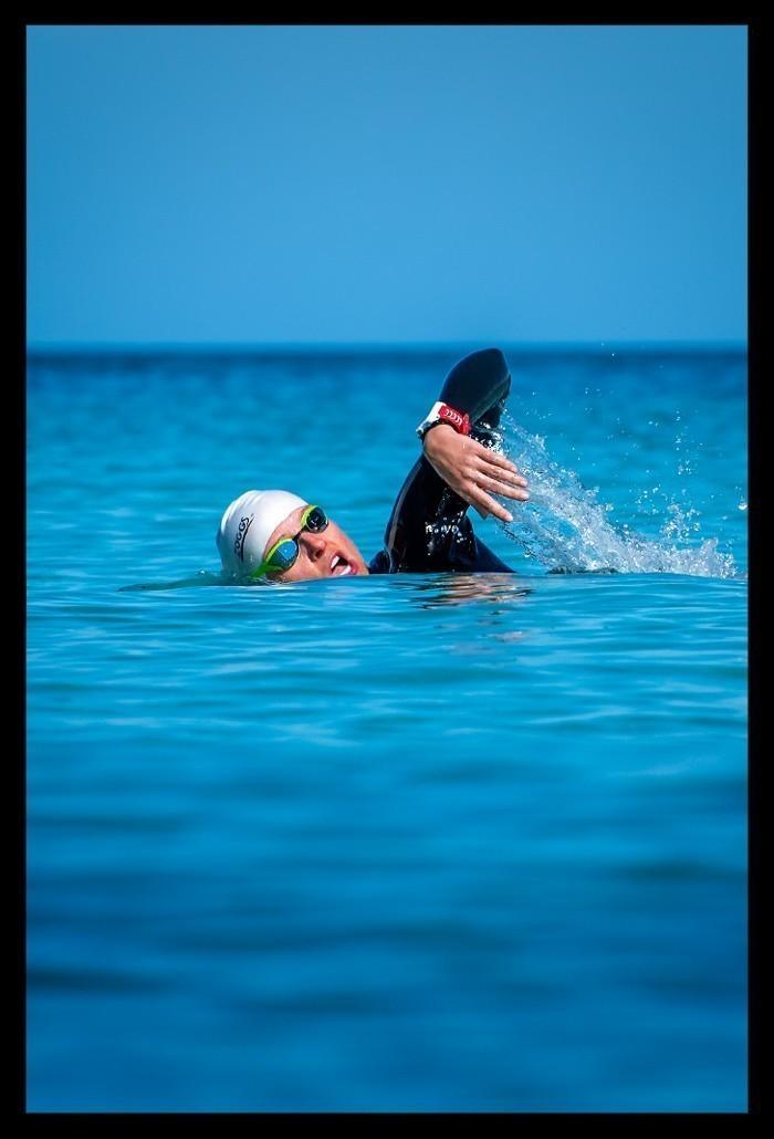 Schwimmtraining Freiwasser Triathlon Training Freiheit Triathletin im offenen Gewässer mit Neoprenanzug, Schwimmbrille, Badekappe und GPS Sportuhr