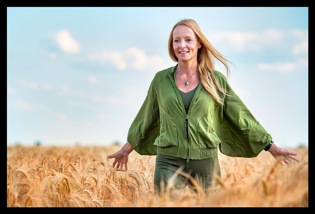 Blonde läuft lachen in grüner Jacke und Tights durch ein Kornfeld vor blauem Himmel mit leichten Wolken