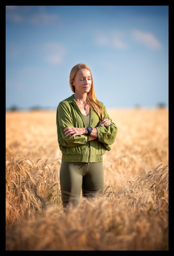 Blonde Frau steht im Korbfeld mit grünen Sachen zum Innehalten Rückzug Achtsamkeit