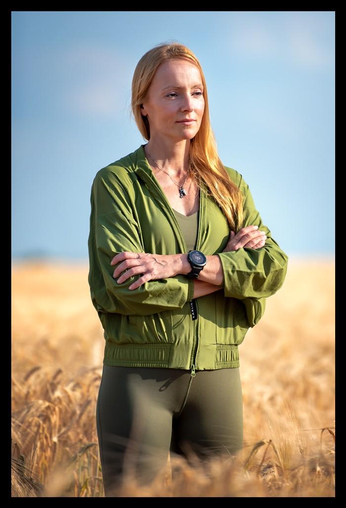 Blonde Sport Bloggerin in grüner Jacke und Yoga Leggings im Kornfeld vor blauem Himmel für den Artikel motiviert bleiben - 8 Säulen zu mehr Motivation Achtsamkeit Triathlon Training