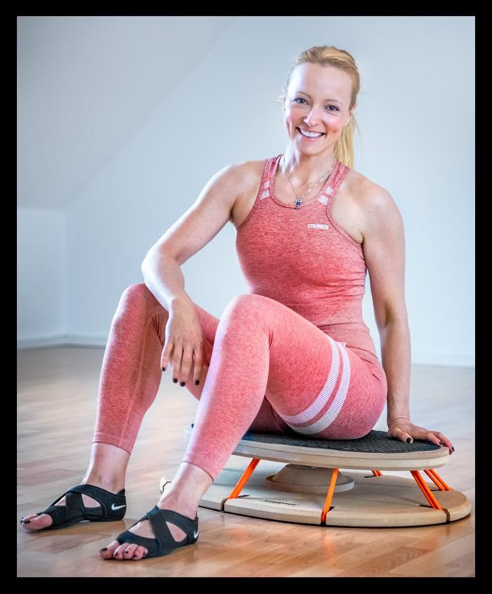 Triathletin Nadin sitzend in Yogasachen in pink auf dem Sensoboard