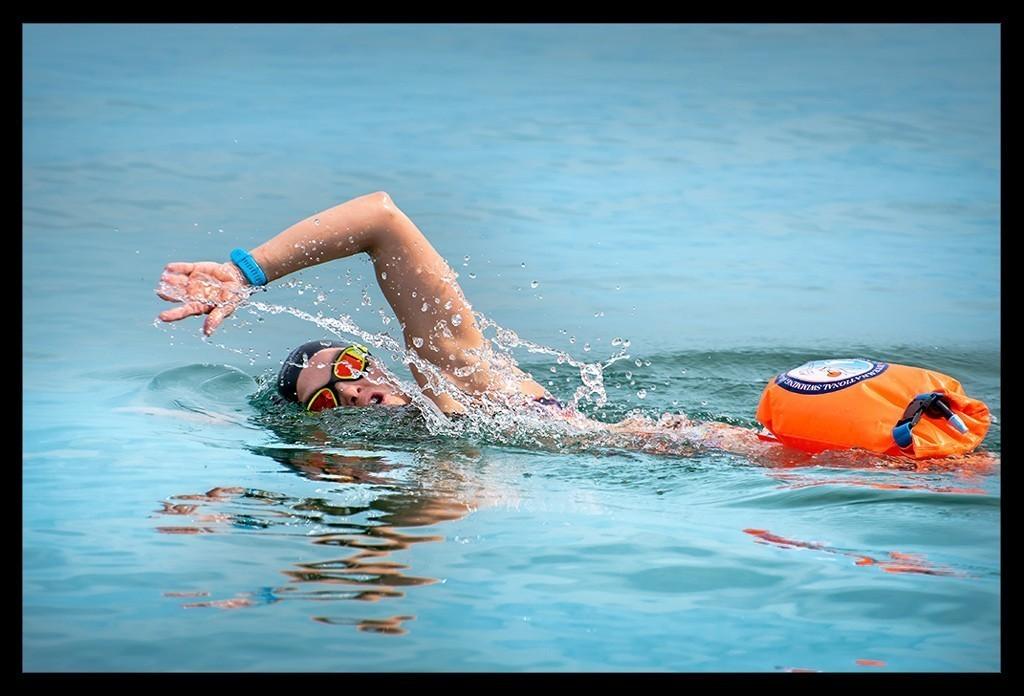 Triathletin beim Freiwassertraining Kraul Schwimmen mit Badekappe, Schwimmbrille, Schwimmboje im offenen Gewässer Meer oder Ozean
