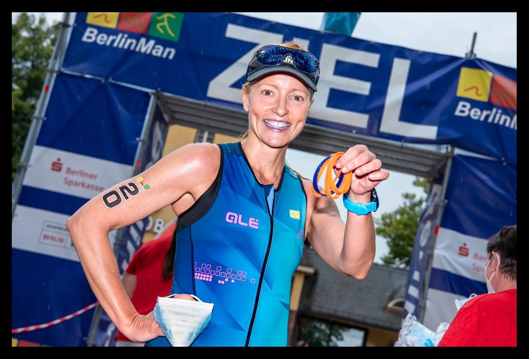 Triathletin beim BerlinMan Triathlon im Ziel lachend mit Rundenbändchen