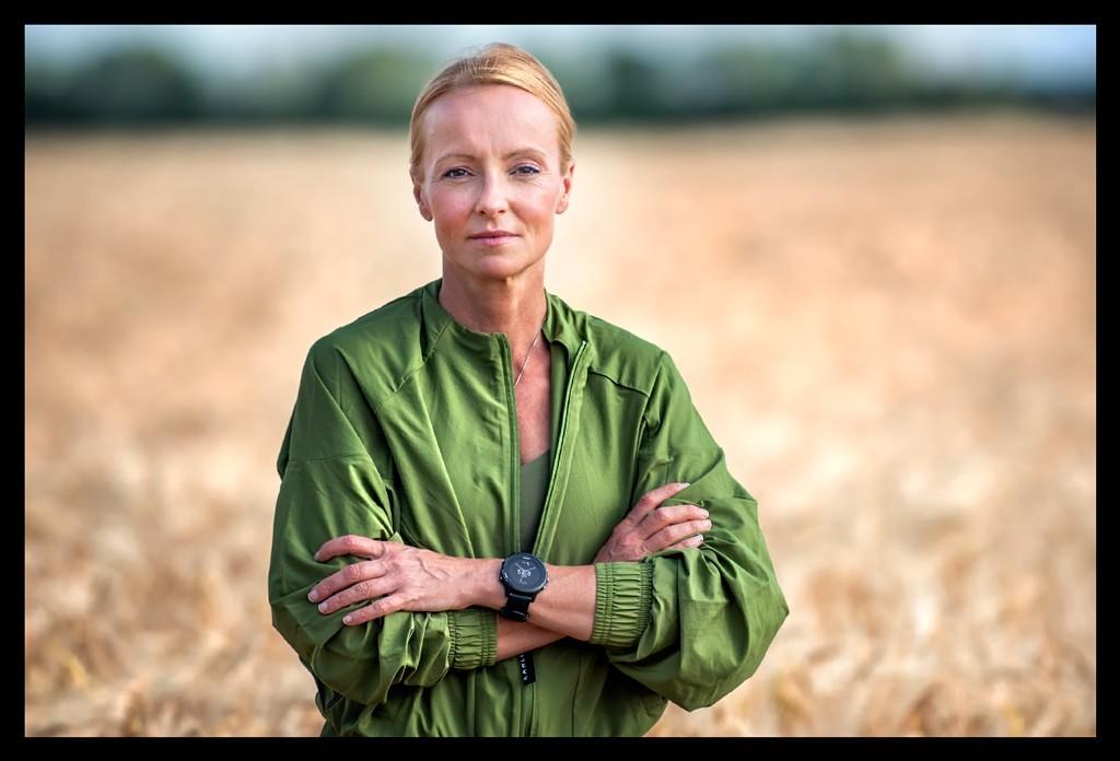 Fitness Bloggerin Nadin Blonde Frau im Kornfeld mit grüner Jacke und Sportuhr