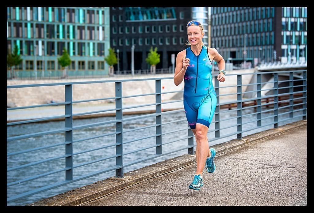 Triathletin und Bloggerin Nadin an der Spree laufend im blauem Tri Suit und blauen Laufschuhen mit Sonnenbrille auf dem Kopf und Sportuhr von Garmin Forerunner 945