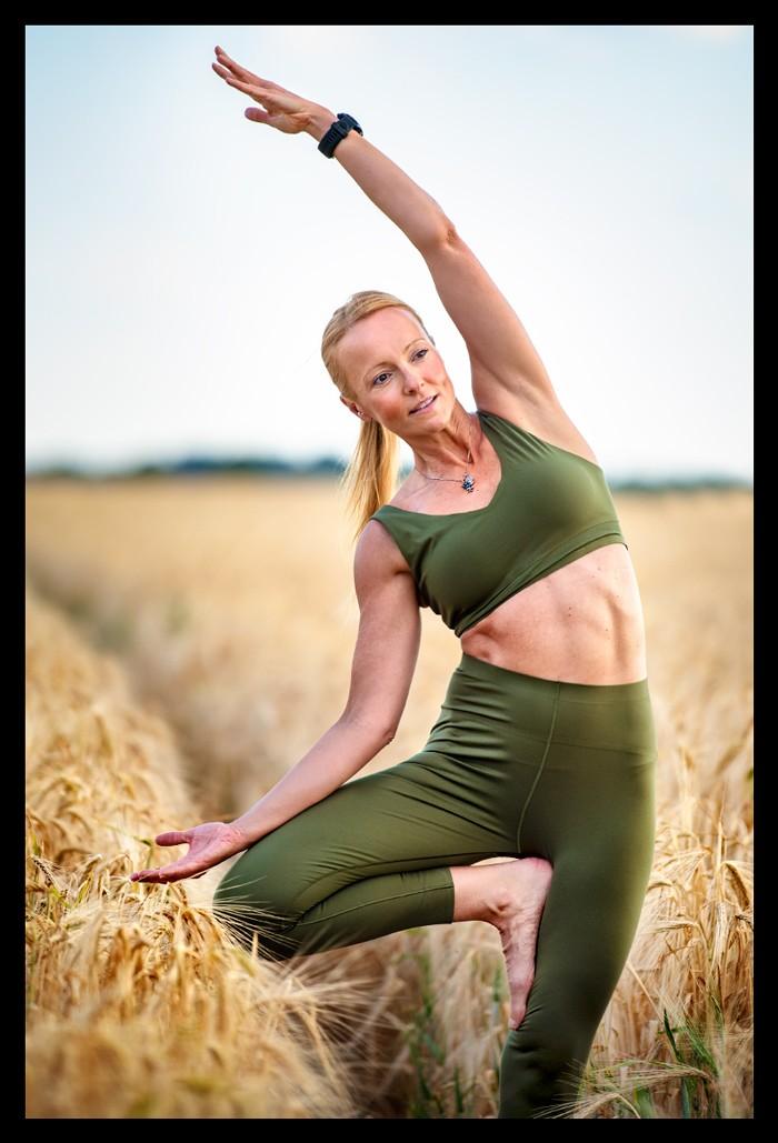Fitness und Yoga Bloggerin Nadin Blonde Frau im Kornfeld mit grünem BH und olivgrüner Yoga Tights mit Sportuhr in Baum Asana