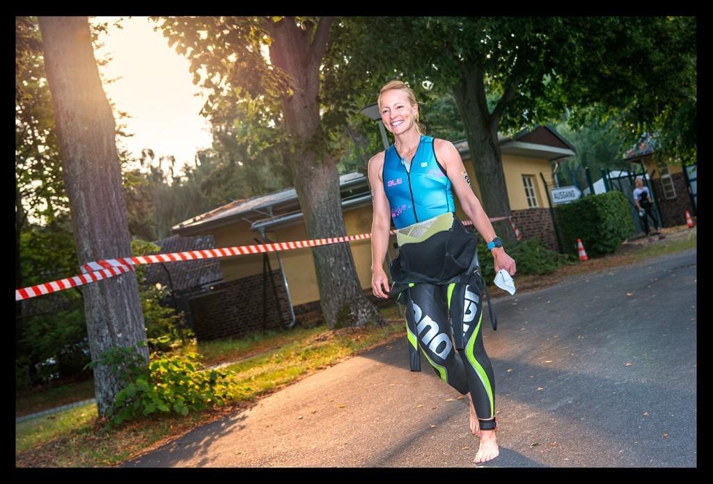 Triathletin und Bloggerin Nadin von Eiswuerfelimschuh vor dem Start BerlinMan Triathlon im Neoprenanzug und Trisuit auf dem Weg zum Strandbad Wannsee laufen bei Sonnenaufgang